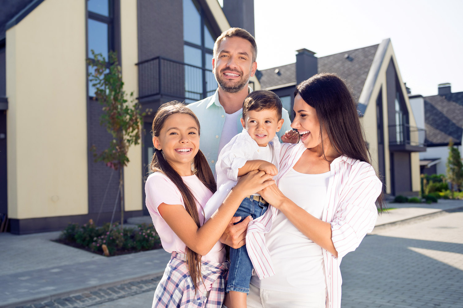 Happy family of four standing together in front of their new house after a home inspection